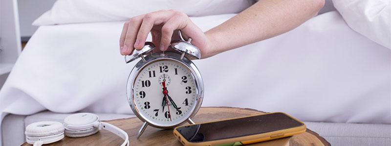目覚まし時計を止める男性の手